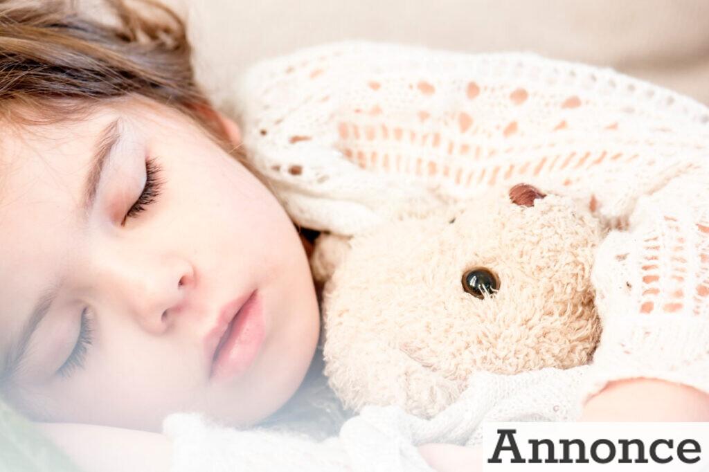 Et sovende barn med bamse